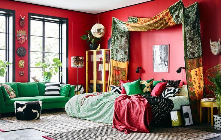 Fröhliche Textilien, bunte Möbel und eine rote Wand sorgen in diesem Schlafzimmer für das gewisse Etwas.