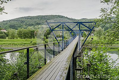 Creative Commons presents hanging over the river footbridge for pedestrians in Small village Rożnów , Poland . Europe.