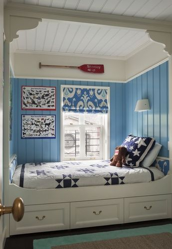 Built in bed with storage or trundle, sconce, paneled walls, quilt, great blue