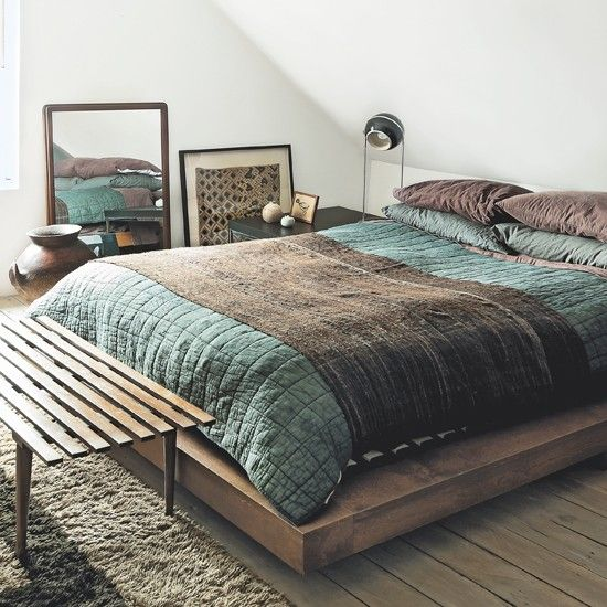 A low platform seems to float in the centre of the pitched-roof bedroom, with a framed African Kuba cloth and a mirror placed at floor level.
