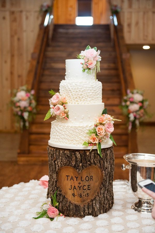 How gorgeous is this rustic wedding cake?!  Love the simple white, the different textures of each layer, and the tree stump base with the couples names engraved! Taken at THE SPRINGS in Edmond.  Follow this pin to our website for more information, or to book your free tour! Photographer:  Holli B Photography #weddingcake #weddingcakeideas #rusticwedding #rusticweddingcake #rusticweddingideas #southernwedding #southernweddingcake #southernweddingideas #uniqueweddingcake