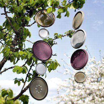 Couvercles de pots de peinture percés et peints pour former des mobiles dans les branches d'arbres