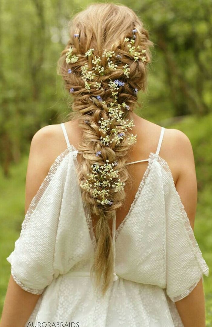 renaissance braids, long blonde messy braid, decorated with lots of tiny white and blue flowers, worn by woman in white off-shoulder lace dress