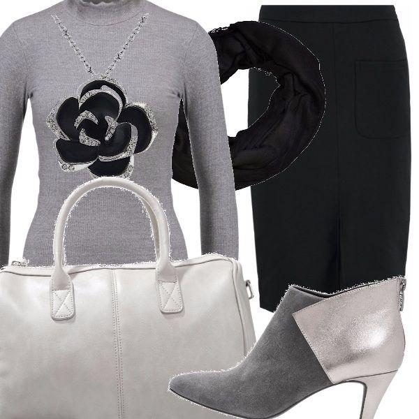 Un ciondolo con un fiore nero campeggia sulla maglia aderente grigia, da indossare sulla gonna con tasche e spacco sul davanti, scarpe con tacco alto, borsa a mano chiara e un foulard intorno al collo.
