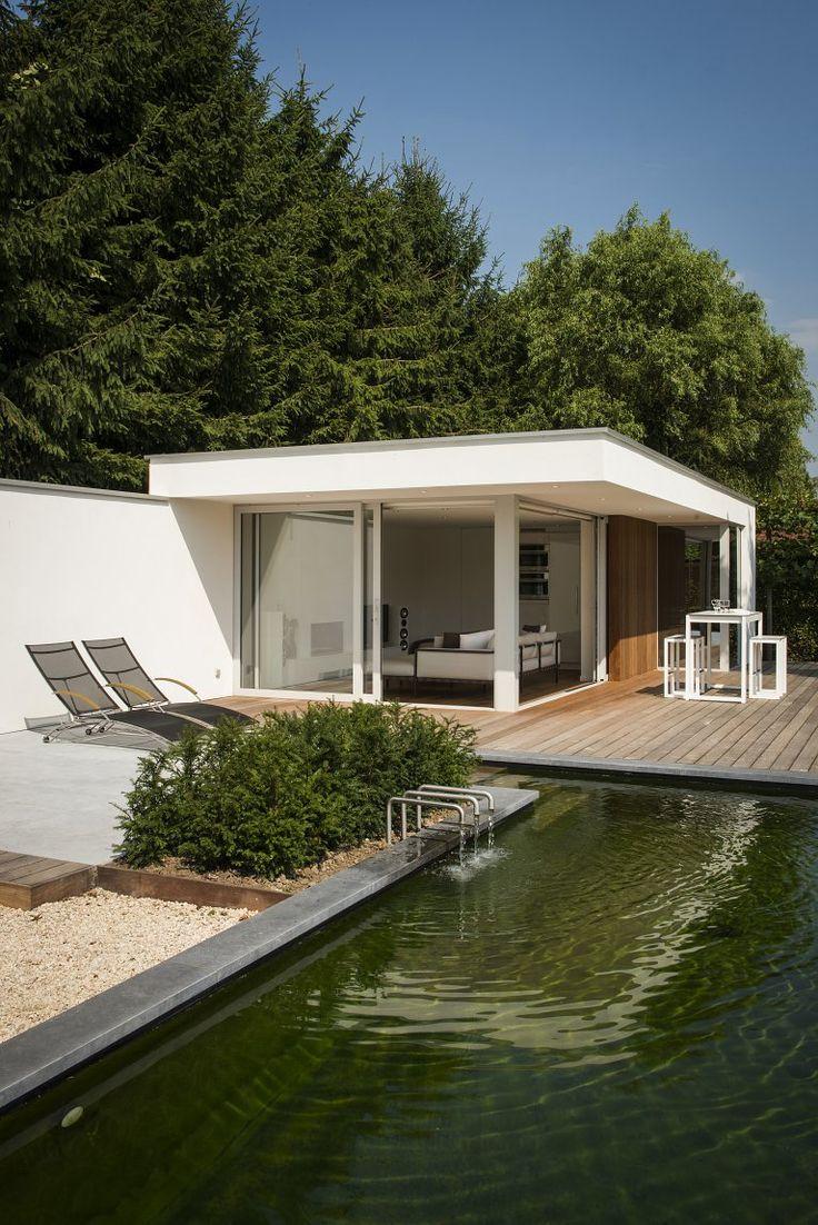 Modern poolhouse in crépi en hout. Poolhouse met wellness en sauna geïntegreerd. Er zit ook een badkamer, kleedkamer en keuken in. Het poolhouse werd gebouwd bij een natuurlijke zwemvijver.