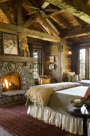 A wonderful rustic lodge bedroom with a fireplace and window...
