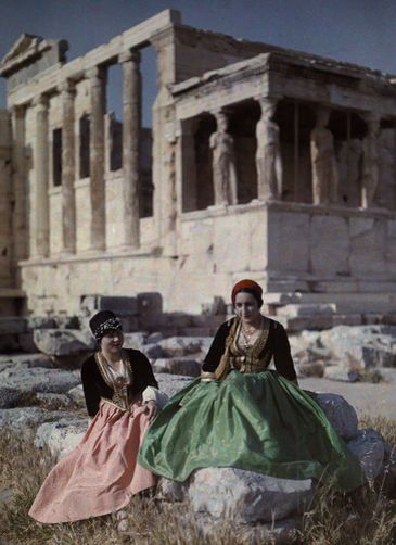 Two women by the Parthenon in the costumes of Crete and Queen Amalie. National Geographic's Greece in Color from the 1920s Photographer: Maynard Owen Williams in the 1920s