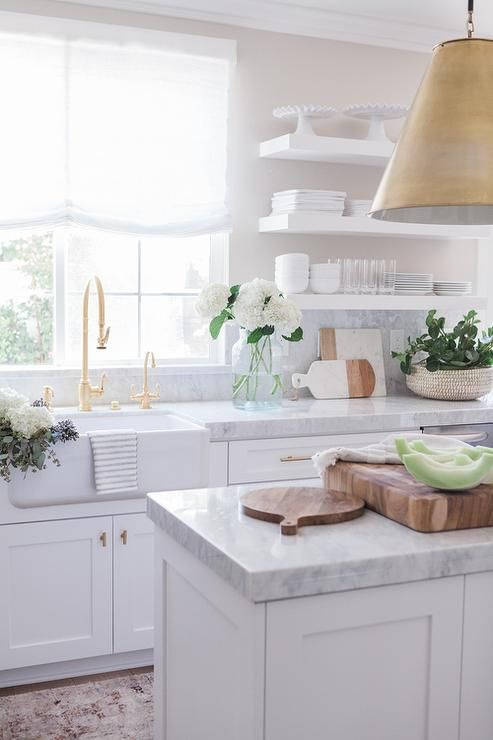 Gorgeous kitchen boasts white shaker cabinets adorned with brass hardware paired with white and gray quartzite countertops and backsplash.