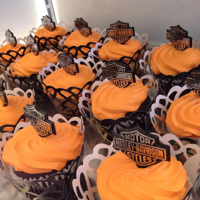 Harley Davidson themes baby shower. Orange frosted cup cakes with Harley sticks and black twirl wraps for cupcakes.