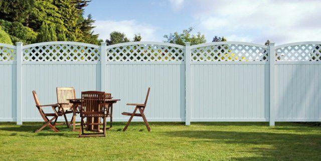 clôture PVC blanche et mobilier de jardin en bois sur la pelouse