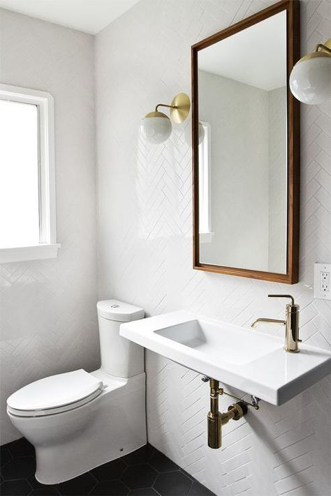"""Black and white bathroom features walls clad in a white herringbone tiles, EliteTile Retro 2"""" x 7-1/2"""" Polished Soho Subway Porcelain Field Tile in White, lined with a West Elm Floating Wood Wall Mirror illuminated by Cedar Moss Alto Sconces over a white porcelain wall-mount sink, Ceramica Tecla Serie 35 Ceramic Bathroom Sink with Overflow, fitted with a Kohler Purist Single-Control Lavatory Faucet with Straight Lever Handle in Vibrant French Gold alongside a black hex tiled floor, EliteTile…"""