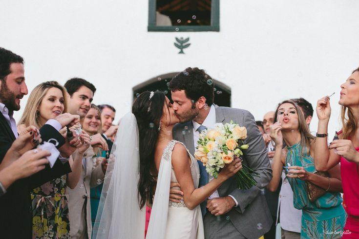 7 indicações incríveis de fotógrafos para casamento que a gente ama. Casamento na praia com bolhas de sabão quando os noivos saem. Buquê de noiva amarelo e verde, noiva morena com véu. Casamento rústico e ao ar livre de dia.
