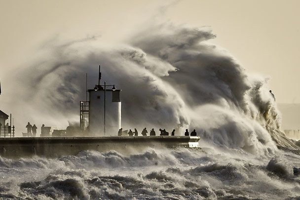 People watch and photograph enormous waves as they break, on Porthcawl harbour, South Wales, Monday Jan. 6, 2014.