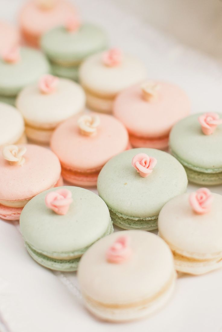 Mint, peach, and cream french macarons with roses as dessert or giveaways