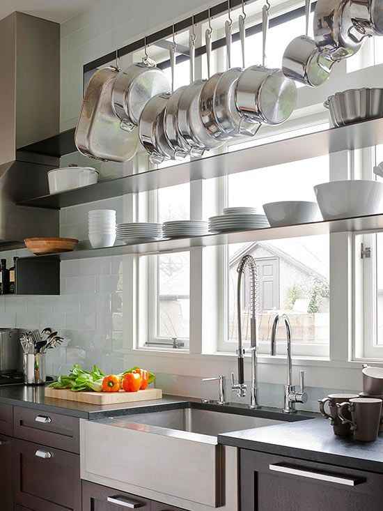 Natural light is a boon in small spaces, helping to brighten dark corners and make tight rooms feel bigger. But windows can also gobble up potential storage spots. To get the best of both window-focused worlds, consider a strategy used in this kitchen: a mid-height shelf for a few short bowls, and a hanging rack near the ceiling for essential pots and pans…