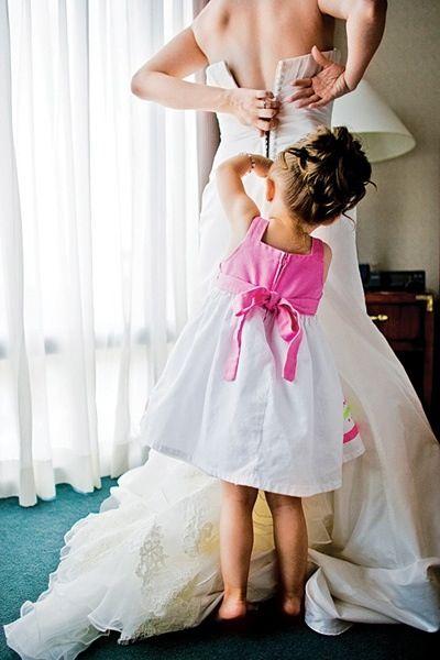 Bloemenmeisje doet de rits van de trouwjurk dicht, leuk shot!