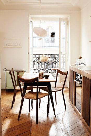 パリ・アパルトマンに欠かせないバルコニー。窓からの太陽の光がインテリアにより美しさを加えてくれています。ウッディでシンプルな家具にもこだわりが垣間みえる、気持ち良く過ごせそうなダイニングの空間。