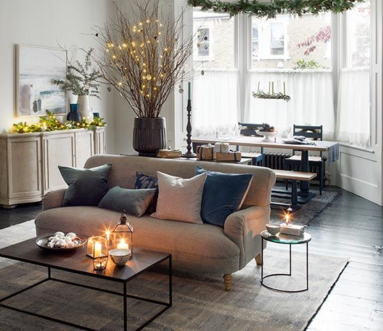 Here, fairy lights have been strung over a twig tree in a large planter to eye-catching effect and entwined with faux garlands to decorate a sideboard. Homes & Gardens. http://www.hglivingbeautifully.com/2015/12/16/the-look-simple-festive-touches/