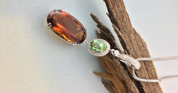 Handmade in 18ct White Gold, this diamond set enhancer showcases a stunning oval Madeira citrine and a stunning oval mint tourmaline, surrounded by small grain set round diamonds. This is a detachable pendant with a beautiful colour combination. Wear it with a chain, coloured gemstone strands, pearls or a neoprene cable.