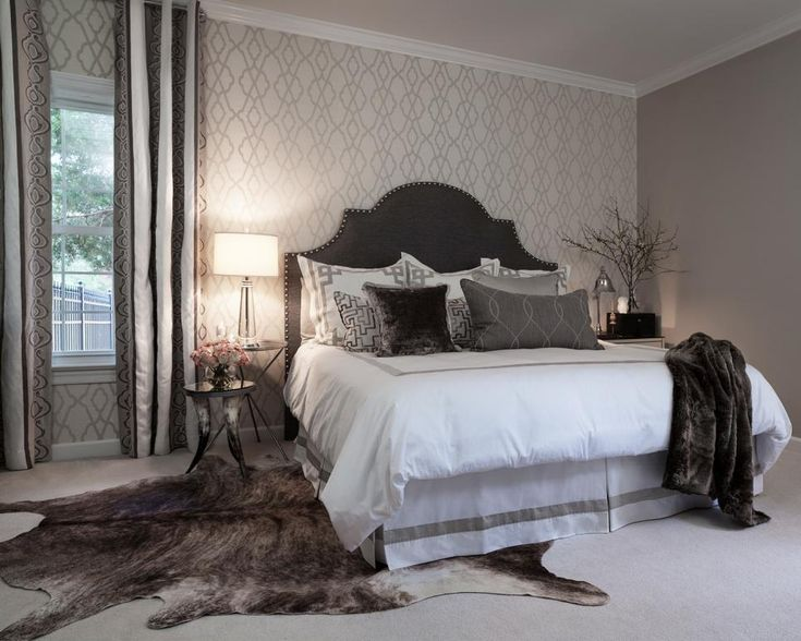 An accent wall with neutral patterned wallpaper adds a subtle graphic touch to this monochromatic master bedroom. The animal skin rug and charcoal-colored headboard create drama in the transitional space.