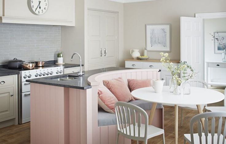 A central island unit can give you extra worktop space, storage and in this case, additional seating. You don't get more multipurpose than that! The banquette creates a comfy place to sit and eat in the kitchen. Curved seating is set into the island and works perfectly with the compact round dining table. Painting the island in a soft rose pink makes it stand out from the rest of the kitchen. Artisan kitchen in Blush (island) and Slip (inframe cabinetry); worktops in Honed Flash Blue…