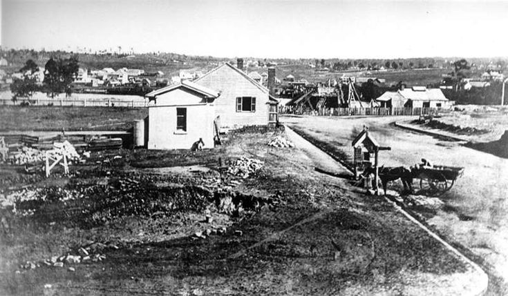 Early view of Brisbane, showing the construction of the first permanent Victoria Bridge in the background, ca. 1872