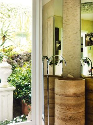 A travertine stone basin is the focal point of the bathroom in this Devonport home.