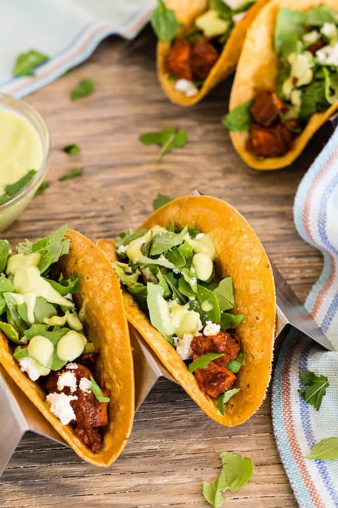 Spicy vegetarian mole tacos with sweet potatoes, arugula, goat cheese, and avocado crema can easily be vegan--skip the goat cheese. Gluten free tacos, via @lettyskitchen