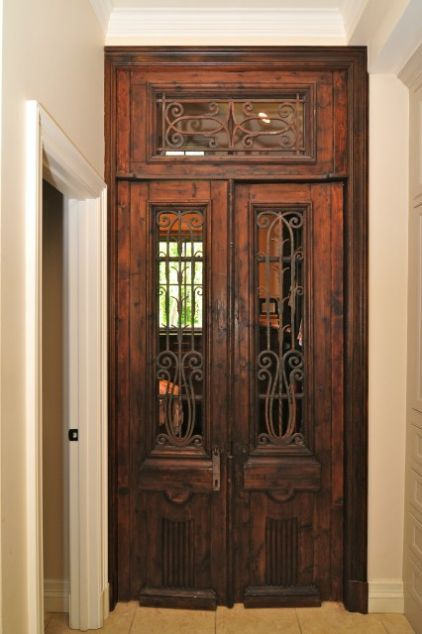 "In the entryway to her husband's wardrobe area from the master bathroom, Blumenfeld installed stunning antique French walnut doors and a transom, all with hand-forged wrought iron details.     ""I discovered these while studying in New Orleans and got them for a steal,"" she says. ""I held on to them over the years, knowing one day I'd use them for a client. That client ended up being me."" she says."