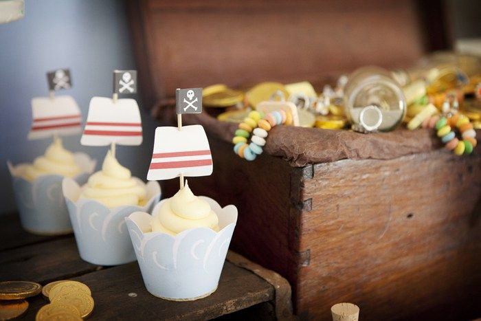 """We're loving this pirate party from Bec and Tammi of RubyJu. The table included """"pirate loot"""" like treasure gold chocolate coins, chocolate milk treasure bottles, pirate cake pops, anchor cookies, and skull treat bags. We love the props like the pirate ship sails, the treasure box, and wooden crates. It looks like the birthday boy …"""