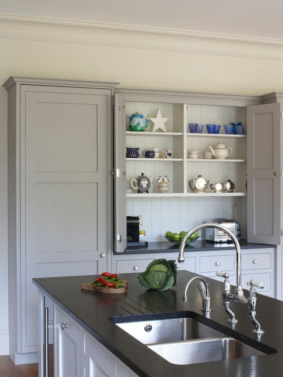 Esher country kitchen design. Large island with integrated sink and large kitchen cabinets.