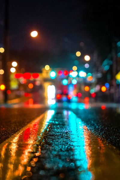 This is a photo of a busy city such as NYC and it is focusing on the road lines with city lights blurred in the background