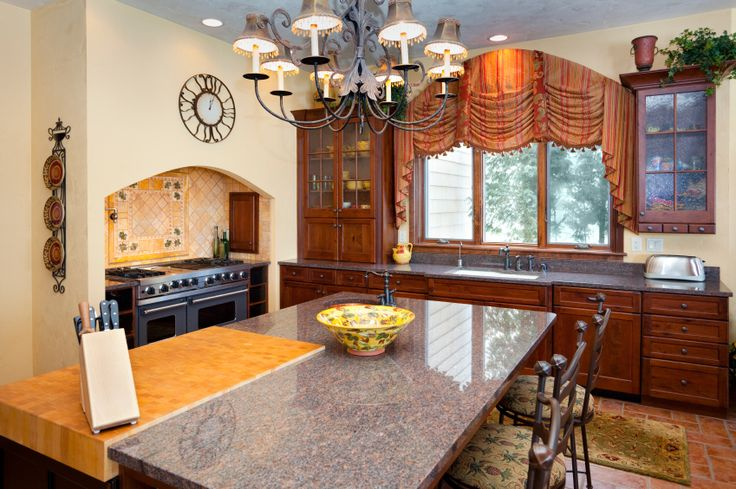 A country kitchen with a butcher block section of the island designed to be used as a cutting board and glass-faced cabinets.