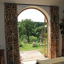 Hand forged poles with specially strengthen brackets were used in order to compliment the barns stonework but also to take the weight of the 5 inch pencil pleat curtains.