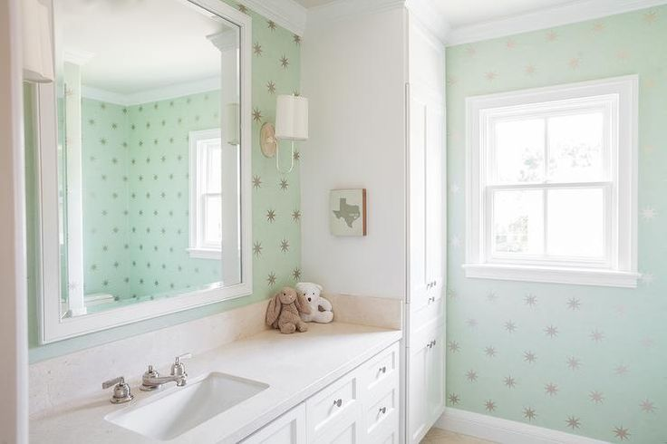 Fun kid's bathroom features walls clad in mint green star wallpaper, Coronata Star Wallpaper, lined with a white sink vanity topped with off white quartz under a white framed mirror illuminated by Barbara Barry Simple Scallop Wall Sconces.