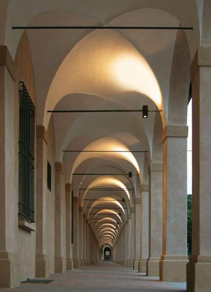 catena | Viabizzuno | cuerpo iluminante para interiores y exteriores IP44 realizado en metal pintado en bronce o antracita. estudiado para ser instalado sobre las cadenas de tracción de los arcos, con una sección máxima de 50mm, catena resulta especialmente indicada para iluminar pórticos e iglesias. mediante un estribo, puede montarse también en pared. aloja un equipado de doble emisión compuesto por un portalámparas RX7s para lámparas de halogenuros máx 70W, o R7s para halógena lineal 200W