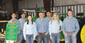 The Falls City Tractor Restoration team, along with the owner of the John Deere B tractor, including (from left) Jon Swierc, Clinton Noll, Katie Johnson, Cody Jendrusch, Jake Hinds, Katie Pollok, and Travis Glover, celebrates earning a blue ribbon during the San Antonio Livestock Show  Rodeo.