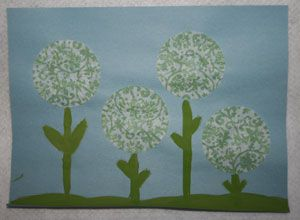•Paint or draw a green line along the bottom of the paper for grass.  •Flatten out your cupcake wrappers and glue to the paper.  •Add stems and leaves under each wrapper to complete your wrapper flowers.