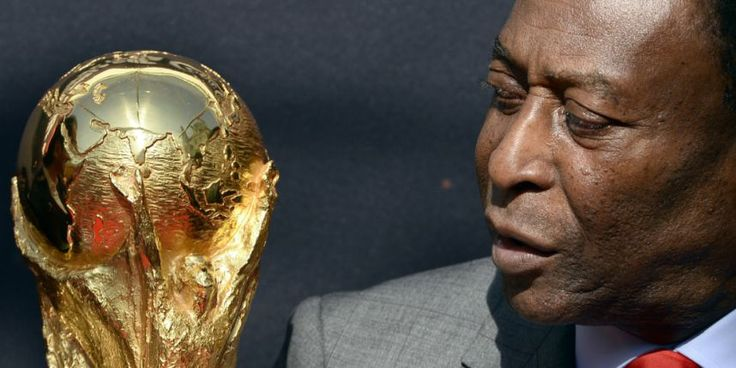 FRANCE, Paris : Brazilian football legend Pele looks at the FIFA World Cup trophy during a FIFA event on March 9, 2014 outside the Hotel de Ville in Paris. The FIFA World Cup trophy arrived with its ambassador Pele in Paris on March 9, 2014 and will be exhibited on the Hotel de Ville plaza until March 10. This event kicks off the festivities of the FIFA World Cup 2014, that will be held in Brazil through June 12-July 13, 2014. AFP PHOTO / FRANCK FIFE
