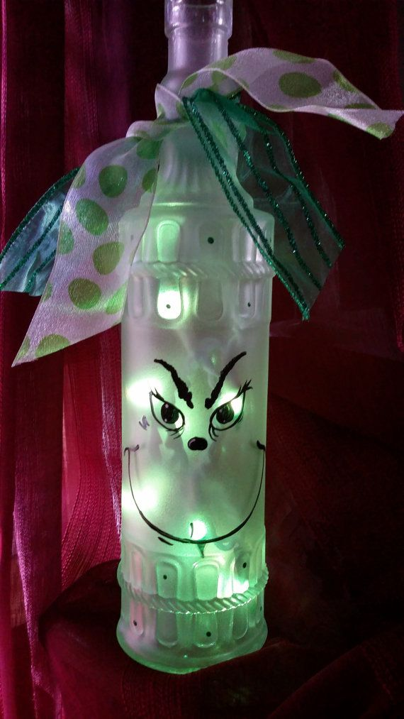This is a frosted wine bottle with a Grinch face painted on it. Green lights are inside and plug-in from the back. The bottle illuminates in a