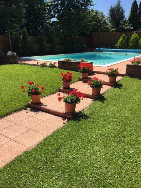 A csodálatosan karbantartott virágos kertben fűthető medence, grillsütő biztosítja a kényelmet. Családi ház, villa eladó Budaliget 400 m² - HomeHunters - Ingatlanok