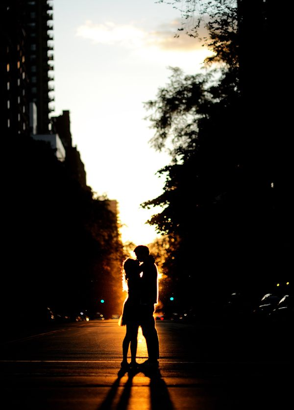 happy couple silhouetted in the late evening sunset - standing in the middle of the street -  photo by New York City based wedding photographer Ryan Brenizer