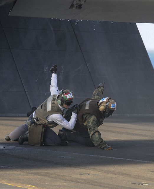 """PACIFIC OCEAN (Dec. 10, 2013) Aviation ET 3rd Class Jonathan Roberts, left, and AOAN James Gibbons, both assigned to the """"Gray Wolves"""" of VAQ 142, signal under an EA-6B Prowler wing as it launches off the flight deck of the aircraft carrier USS Nimitz (CVN 68) during the departure of Carrier Air Wing (CVW) 11. CVW-11 fixed wing aircraft flew off Nimitz to return home after more than eight months deployed to the US 5th, 6th and 7th Fleet AORs. (U.S. Navy photo by Kelly M. Agee/ Released)"""
