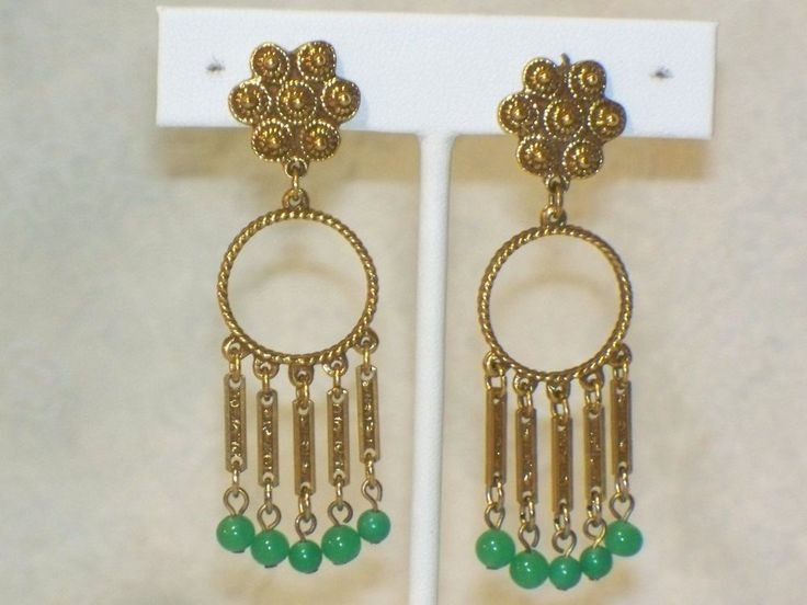 "These gold-tone, gypsy-style earrings have beautiful, green glass dangles. The metal has a pretty textured finish with an ""antiqued"" look. The glass dangles have a rich, jade-green color. One dangle has a small defect within the glass which shows up as a small dark spot but the beads are on wires and are constantly rotating with the wearer's movement (see last picture). 