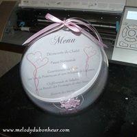 Voici le prototype d'un menu de mariage réalisé en blanc, rose et gris, avec le menu à l'intérieur d'une boule plexi de 16cm, des billes de couleurs dans le fond et du ruban sur le dessus. Le...