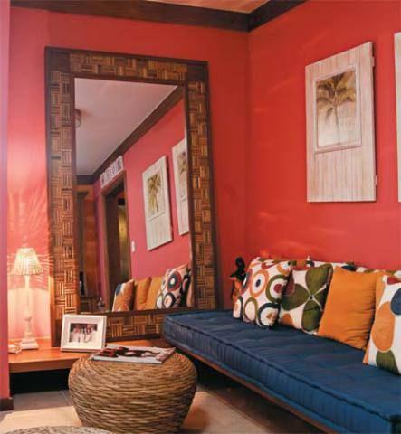 O espelho tem moldura de madeira certificada com moldura de fibra de dendê. O rosa e o laranja usados na parede inspiraram a escolha dos tecidos estampados que trouxeram outras tonalidades, como o azul do futon. Projeto de Mila Regina e Rosa Brandão.