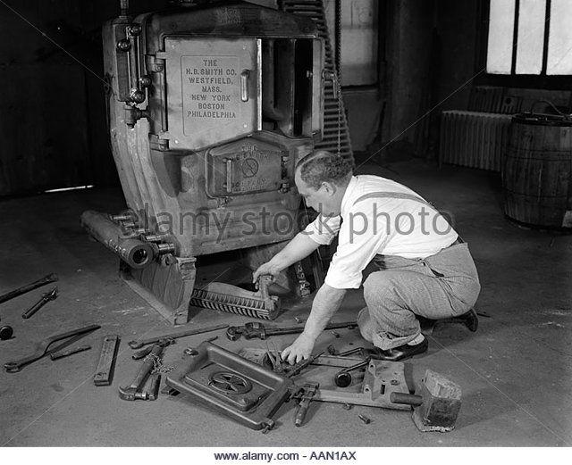 1930s Man Plumber Converting Coal Burning Furnace To Gas