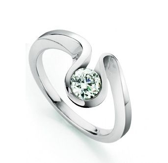 A voluptuous curve of 18ct white gold encases a single sparkling diamond. The wave is a unique and unusual engagement ring design which flows around the diamond, showcasing its brilliance and life and bringing a contemporary twist to the classic diamond ring. 18ct white gold and diamond ring