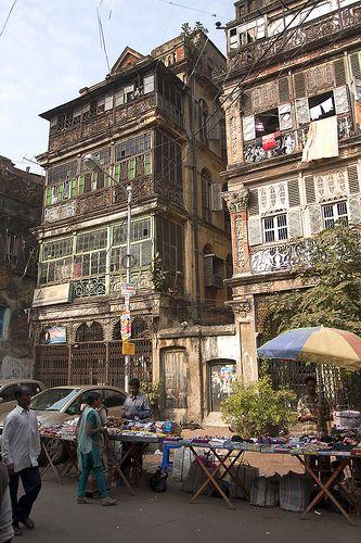 Calcutta Street: elevation, facade, umbrella, windows, vendor; grey, tan, dark, yellow.  This is where my dad is from.