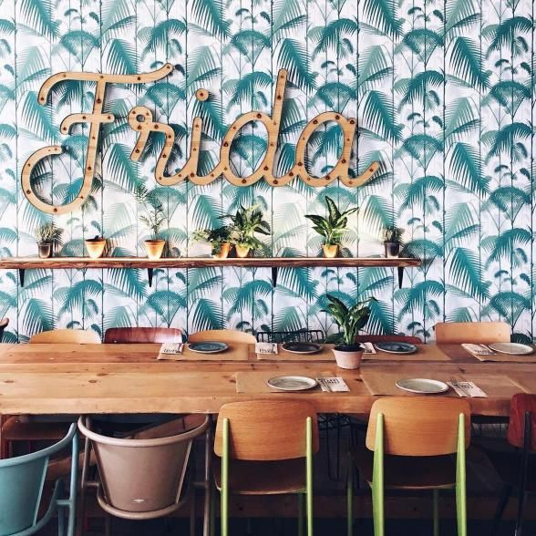 A beautiful Madrid dining spot, Frida has a light and airy feel that's inviting and relaxing. Adding a dash of lush, the tropical palm printed wallpaper is equally crush worthy. | Photo Credit: luisitopin